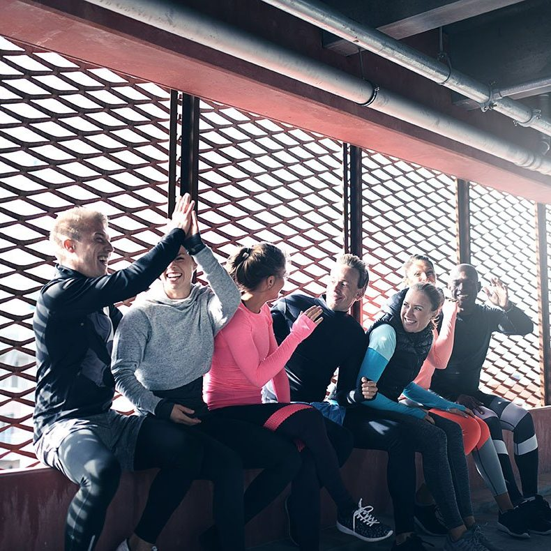 Side view of young people in sportswear sitting in front of bright window and having fun. Copyspace